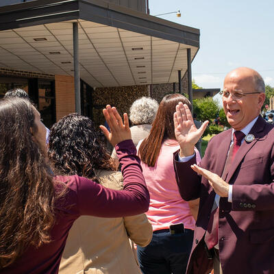 President Dr. Shaw, smiles and lifts his hand as he prepares to high five a student