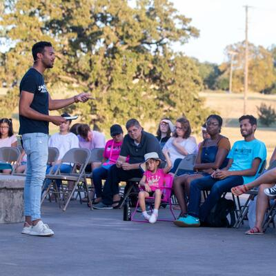 A student pastor stands in front and preaches to a crowd of seated students