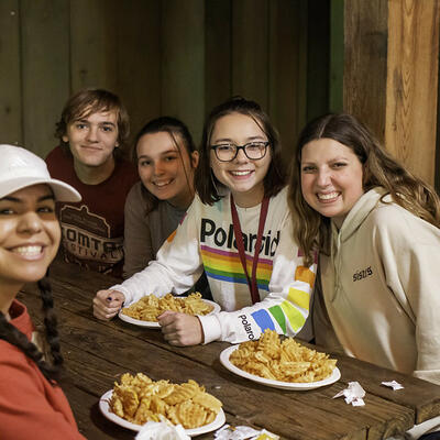 Five students, sitting at a wooden rectangle table, gather together and smile with plates of waffle fries in front of them