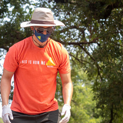 A male student, wearing an orange t-shirt and a bucket hat, looks down as he prepares to pick up something with gloves.