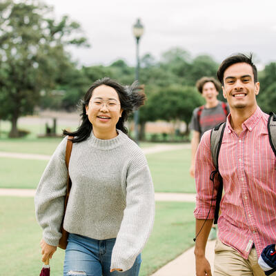 Two students look up and smile as they walk together on campus
