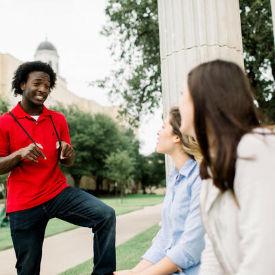 Sitting at the rotunda, two students look up as they talk to their friend stopping by