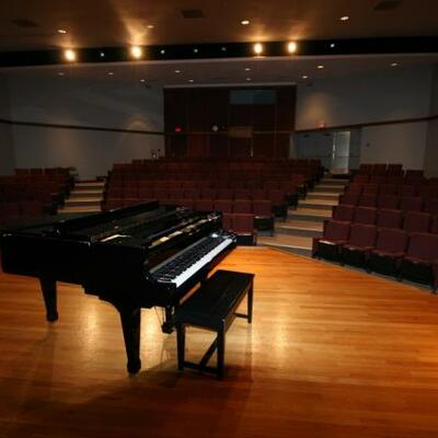 A black, shiny piano sits on a wooden stage in front of maroon chairs installed in the auditorium