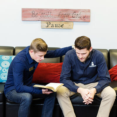 Sitting on a couch, two students sit together and bow their heads as they pray