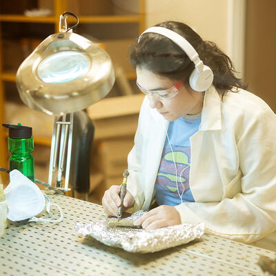 A student wearing a lab coat, goggles and headphones looks down as she focuses on cleaning a fossil