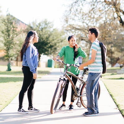 Two students stand on the sidewalk as their friend gets off her bike to greet them