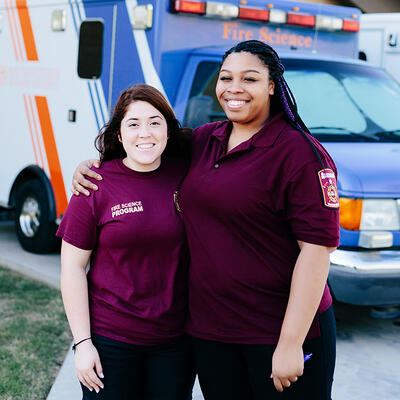 Matching in maroon EMT unifroms, two friends smile and put their arms around each other in front of the paramedic vehicle