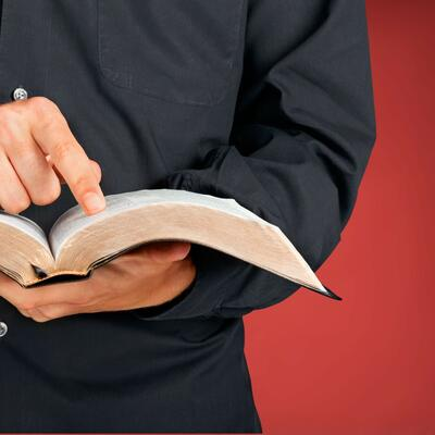 A man dressed in a black button-up holds a bible with one hand and points to a specific verse