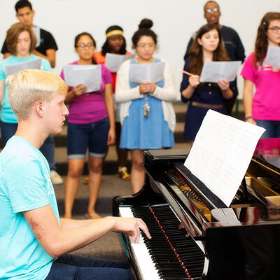 A pianist reads sheet music while playing for the choir that is practicing behind him