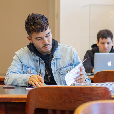 A student sits at the library table and flips through some papers as he studies