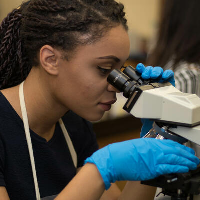 A student wearing blue gloves looks down at microscope as she inspects bacteria