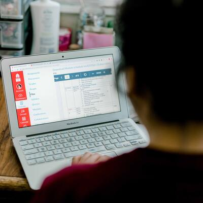 A student opens her laptop and goes to SWAU's academic portal known as Canvas
