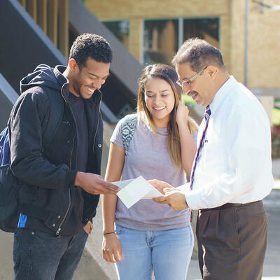 Students speaking with a professor and reviewing paperwork with students outside