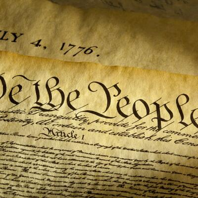 Two old documents with a yellow tint read the beginning words of the constitution