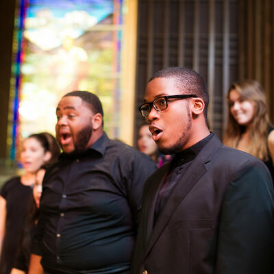 A young man, dressed in all black, join his peers as they look toward their director and sing