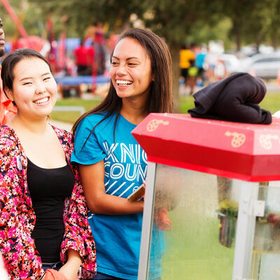 Two students smile and laugh as they wait in front of the popcorn machine