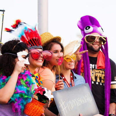 A group of five swau students smile big as they wear silly hats, glasses and other props for a photo