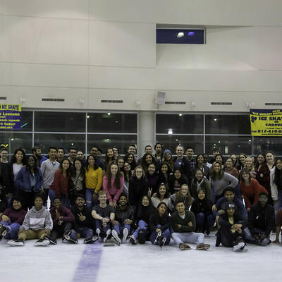 A large group of students smile big as they huddle for a group photo on the ice of the ice skating rink