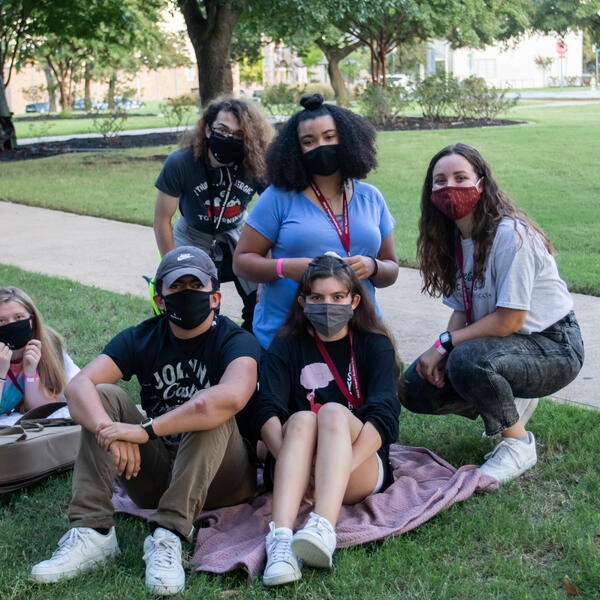 Sitting on blankets outside, six friends gather close and smile big under their face masks
