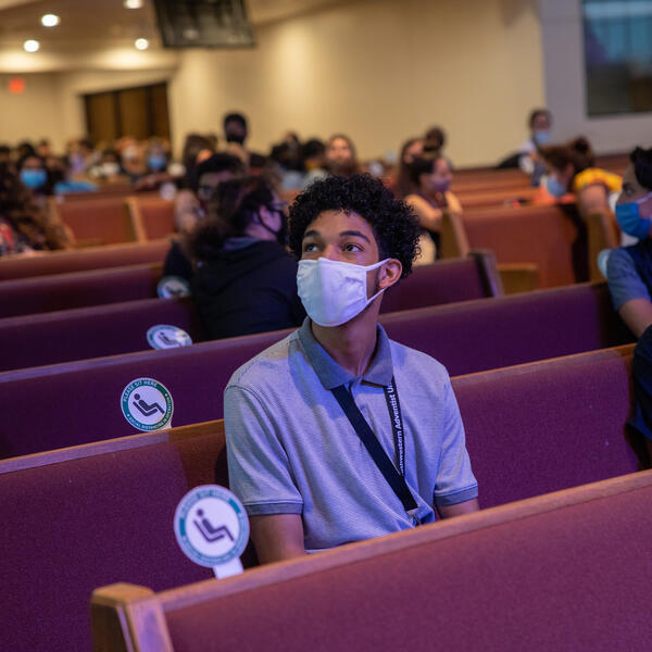 Students wearing face mask sit distanced in maroon pews in the church and look up