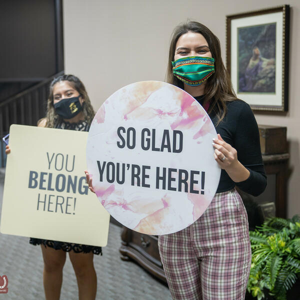 Two female students wearing masks hold up signs with welcome greetings at vespers