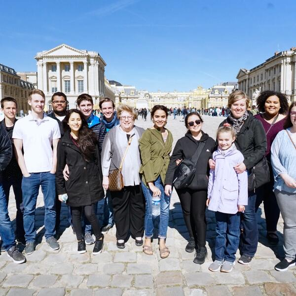 A group of students stand in a group and smile together as they stand in front of palace