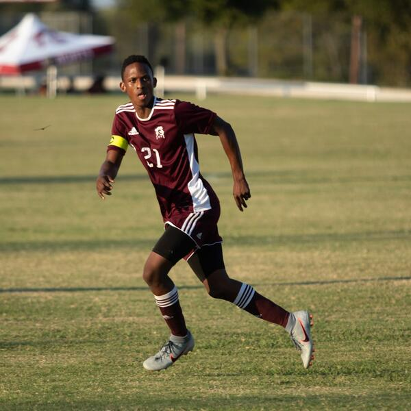 A soccer player in unifrom runs acrross the field during a game and is very focused