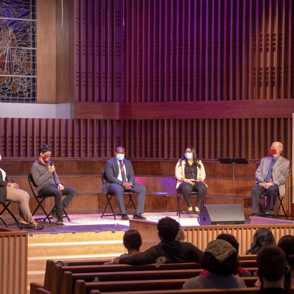 Group of 4 Southwestern Adventist University faculty/staff and 2 students sitting socially distanced on a stage