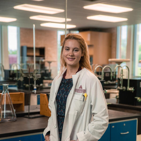 """Kelsey Johnson poses in the lab wearing a lab coat that reads """"Southwestern Adventist University Chemistry"""" with her hands in her pockets"""