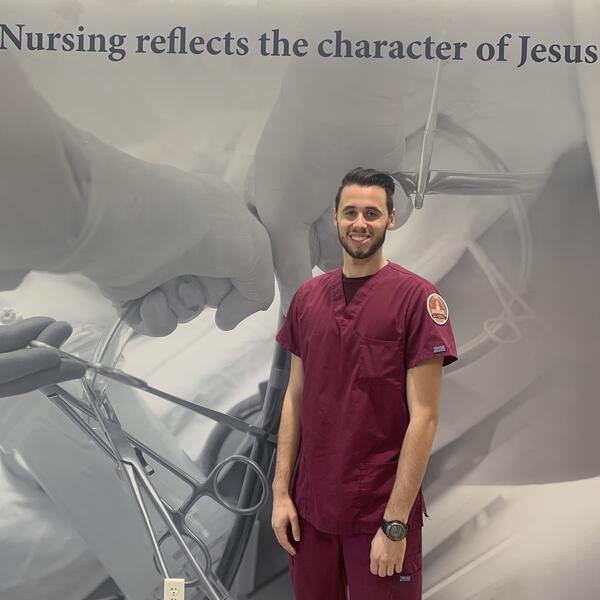 Male nurse student smiles as he stands in his maroon scrubs