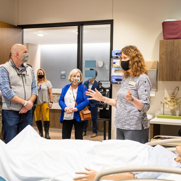 Dr. Kimbrow talking to a group of people touring the nursing simulation lab