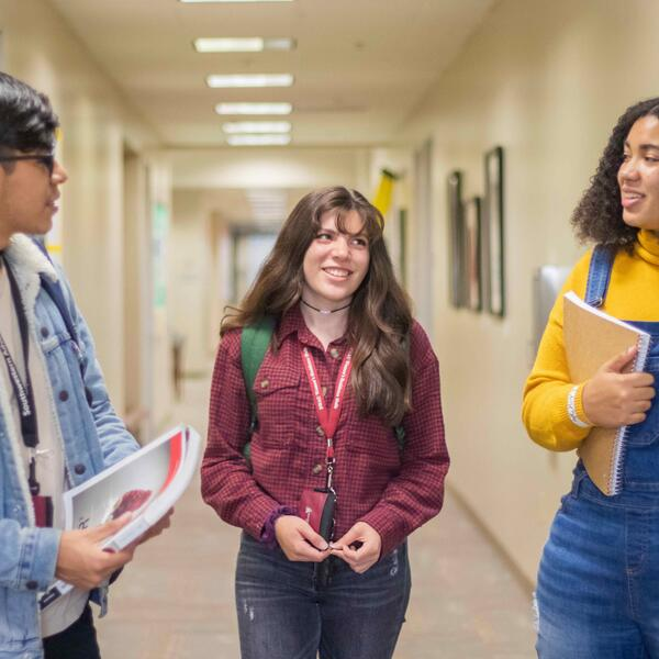Three students stand in a hallway with books, talking