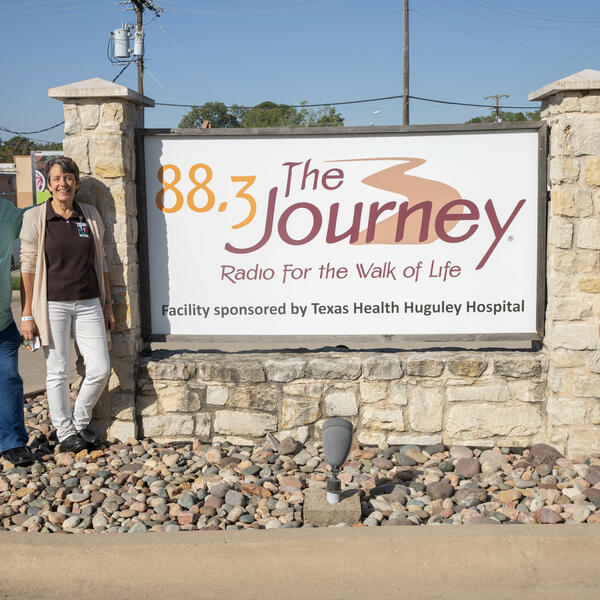 "Mike and Wanda Agee stand to the left of the radio station sign that reads ""88.3 The Journey, Radio for the Walk of Life."" Danae stands to the right of the sign."