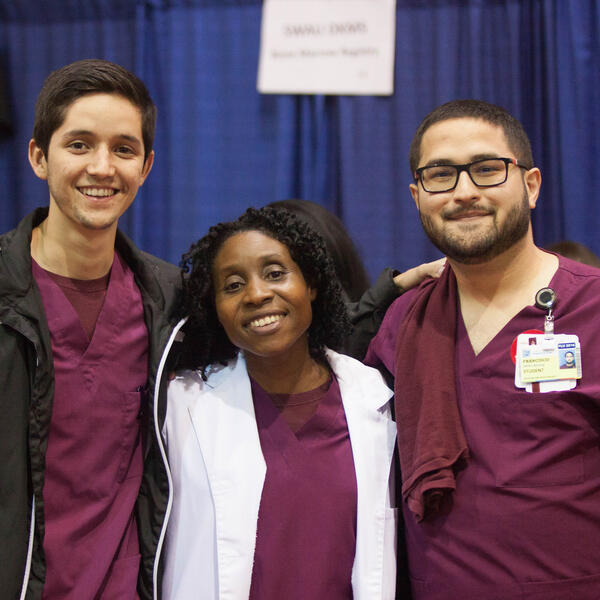 Three people dressed in SWAU scrubs pose in front of navy blue curtain