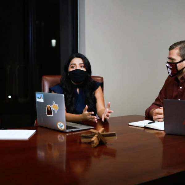 Three people wearing masks sit around a table with computers having a conversation