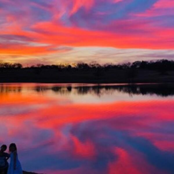 Reflecting off of a pond, the sun sets with bright colors of yellow, orange, pink, blue and purple