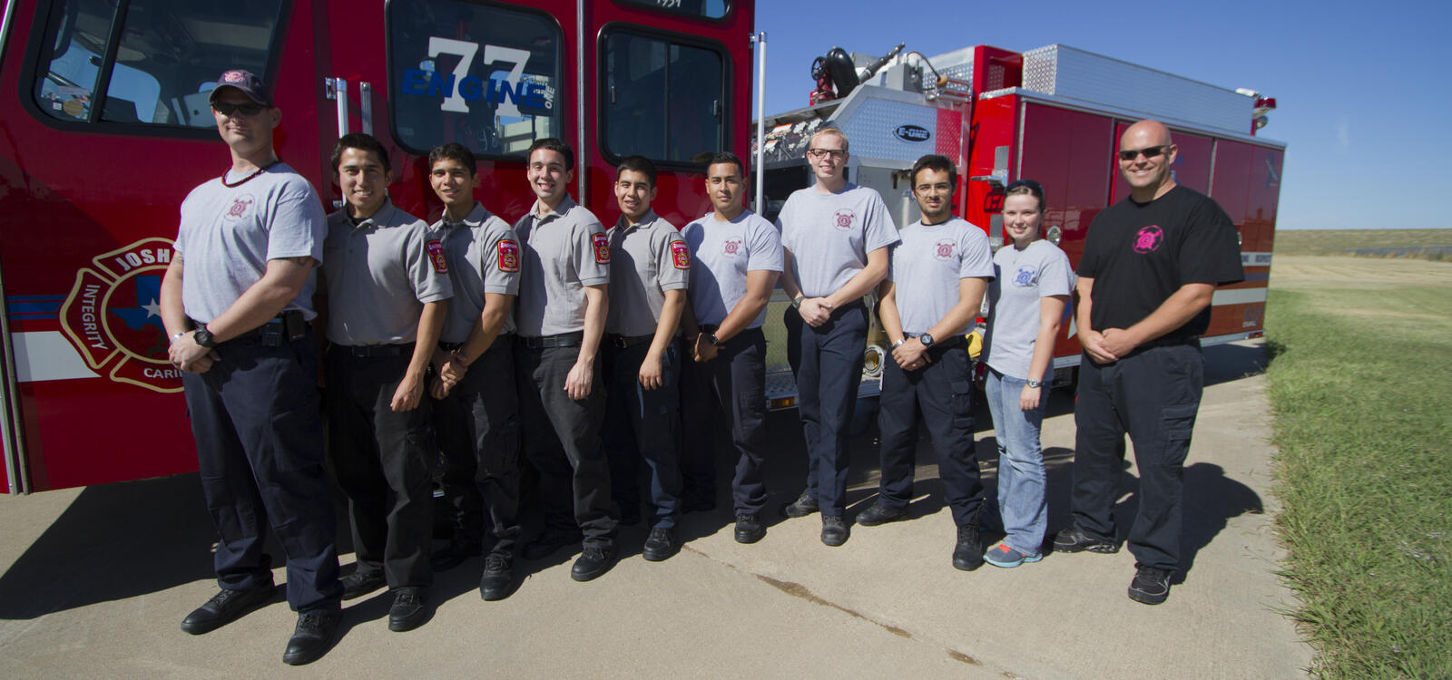 A group of students, matching in gray shirts and dark colored pants, smile as they stand in front of a firetruck