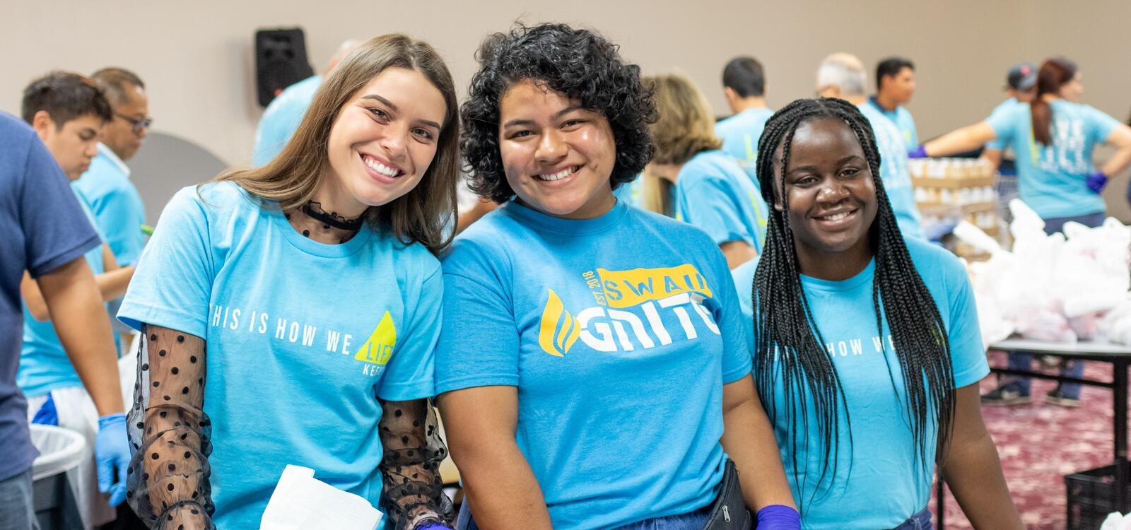 Matching in teal shirts, three women smiles big as they lend a helping hand to the local food bank