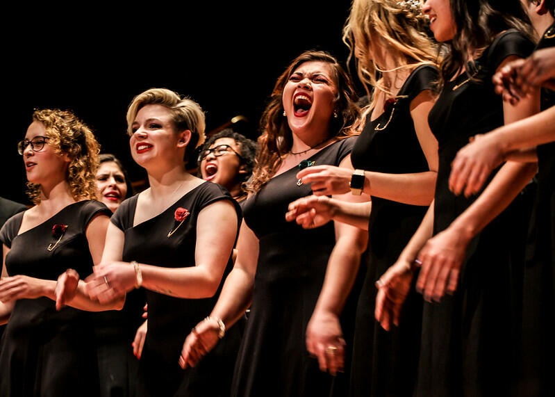 Matching in long black dresses, the women in the choir and laugh and they practice before their event