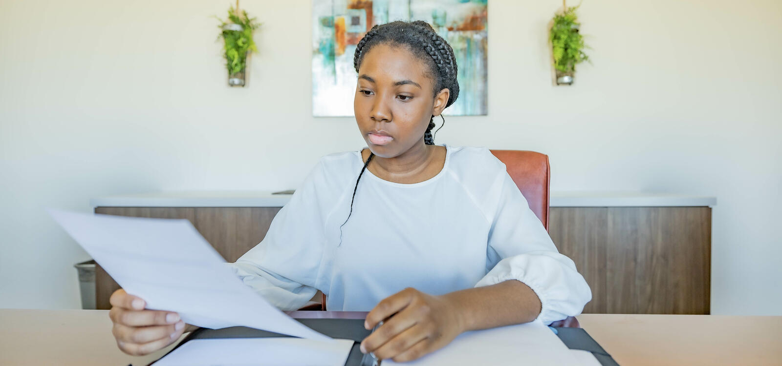 Young, female student dressed in business professional clothes, carefully looking at reports in her portfolio.