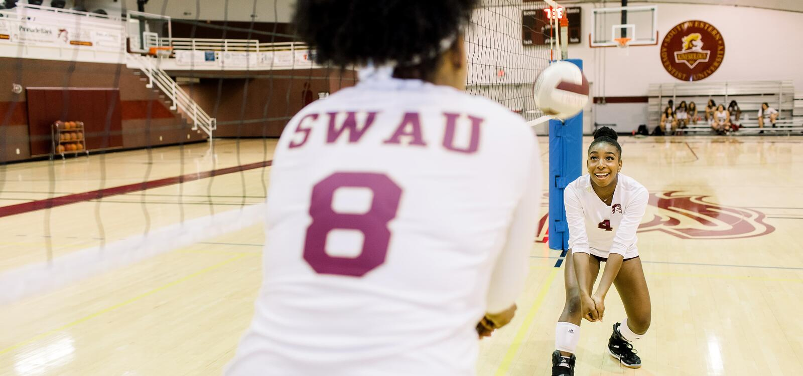 Two volleyball players volleying the volleyback back and forth and smiling