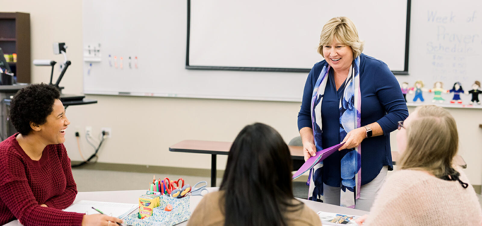 A professor laughs as she stands in front of three seated students who are interacting with her