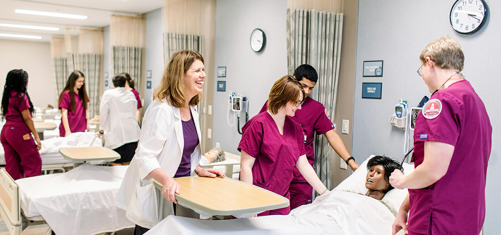 Three nursing students dressed in maroon scrubs look down at their patient and their professor watches over and smiles
