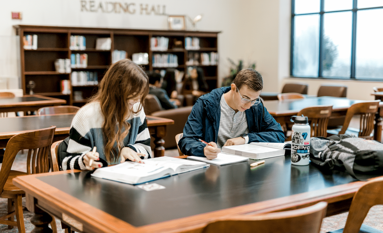Two students sit at the library table as they read their textbooks and write things down in their notebooks