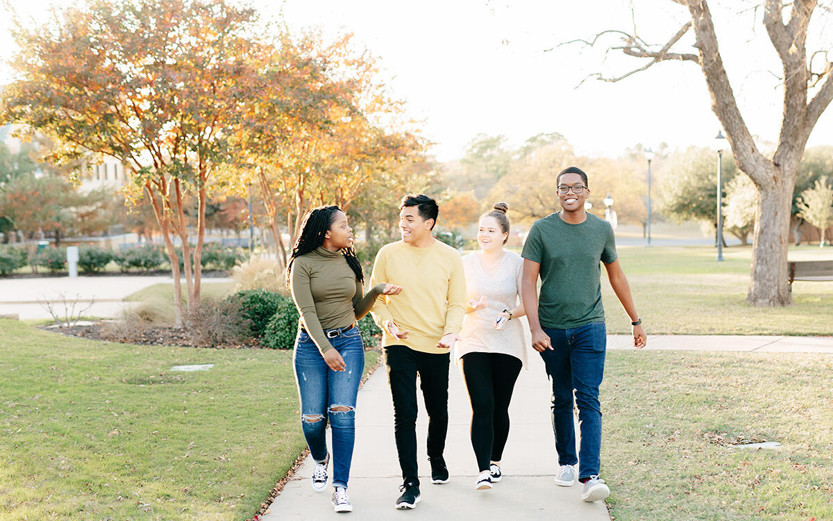 Four students walking on the sidewalks of campus together