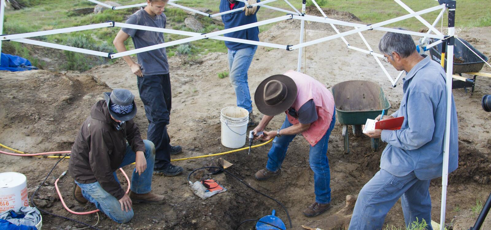 Under a tent, a group of men look down as they use different tools to excavate the burried bone before them