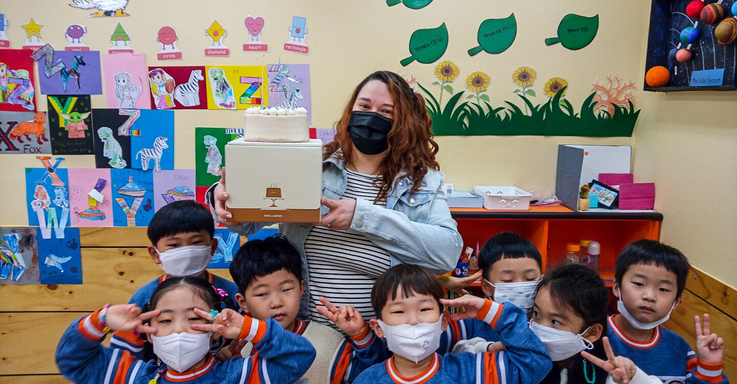Deanna holds up a box with a cake on top in a group of young students in a classroom