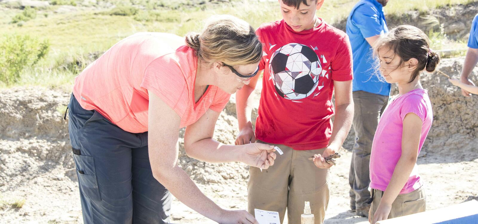 A woman bends down and grabs a label and hands it totwo kids that are out finding a dinosaur bones at the dig site