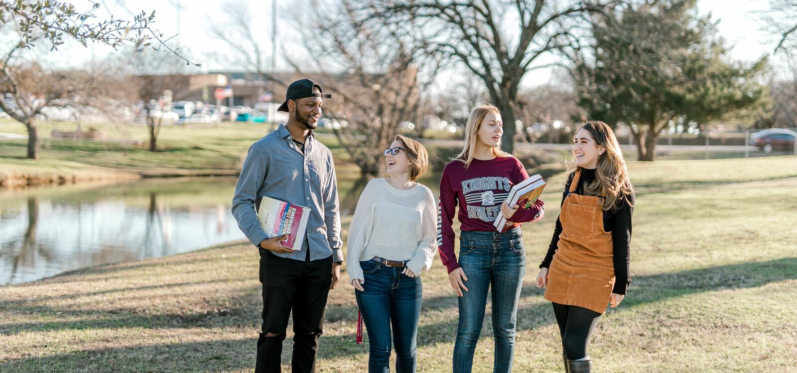 Four students, two with books in hand, laugh as they talk and stand in front of the duck pond.