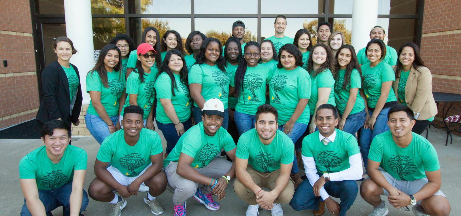 Dressed in matching green t-shirts, a group students stand in four rows and smile